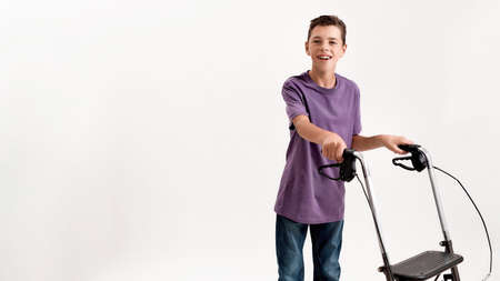Happy teenaged disabled boy with cerebral palsy smiling at camera, taking steps using his walker isolated over white background
