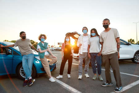 A group of young well-dressed friends of different nationalities having a good time together outside wearing masks standing on a parking site with their cars on a background
