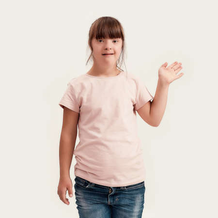 Portrait of disabled girl with Down syndrome smiling while waving at camera, standing isolated over white background
