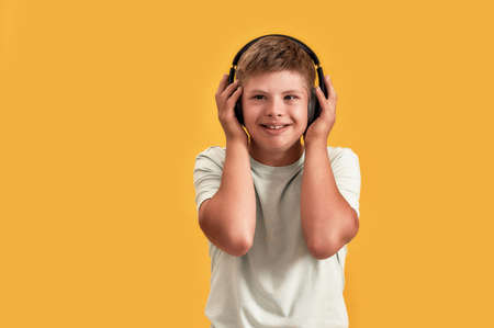 Happy disabled boy with Down syndrome in headphones listening to music and smiling aside while posing isolated over yellow background Stock Photo