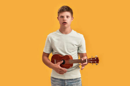 Teenaged disabled boy with Down syndrome looking at camera while playing ukulele, standing isolated over yellow background