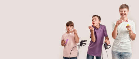 Three cheerful disabled children with Down syndrome and cerebral palsy smiling while blowing soap bubbles, standing together isolated over white background Stockfoto