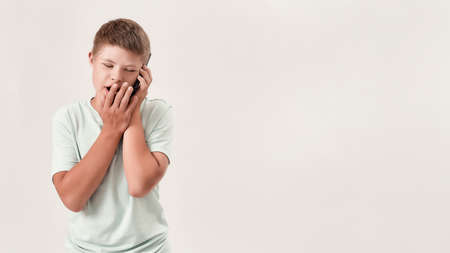 Portrait of teenaged disabled boy with Down syndrome talking on the phone, standing isolated over white background