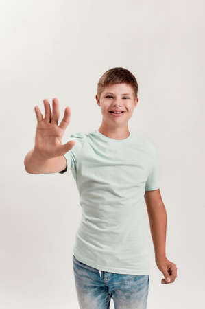 Happy disabled boy with Down syndrome smiling and reaching out his palm towards camera while posing isolated over white background 版權商用圖片