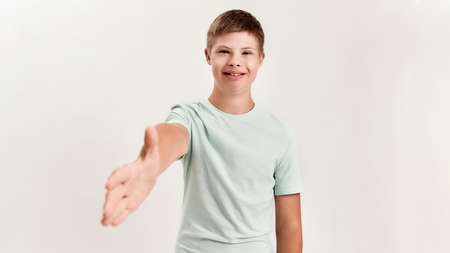 Happy disabled boy with Down syndrome smiling and reaching out his hand towards camera while posing isolated over white background