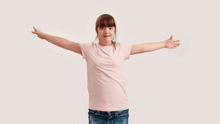 Portrait of disabled girl with Down syndrome smiling at camera while standing with outstretched arms isolated over white background