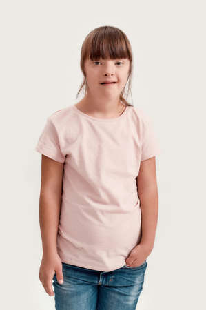 Portrait of disabled girl with Down syndrome looking at camera while posing isolated over white background Stockfoto