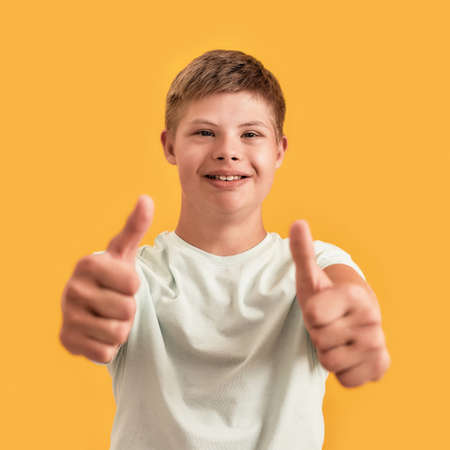Close up of cheerful teenaged disabled boy with Down syndrome smiling at camera, showing thumbs up while standing isolated over yellow background