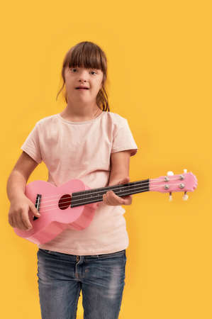 Portrait of disabled girl with Down syndrome looking at camera while playing ukulele, standing isolated over yellow background