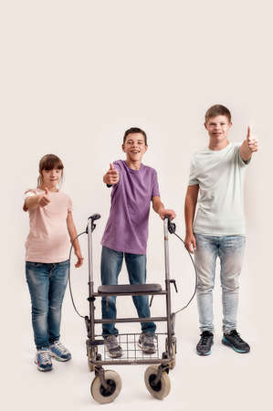 Full length shot of three disabled children with Down syndrome and cerebral palsy smiling, showing thumbs up while standing together isolated over white background