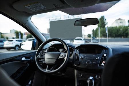 Autocinema screen viewed through front window of empty car