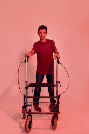 Full length shot of teenaged disabled boy with cerebral palsy looking at camera, taking steps with his walker isolated over red light background