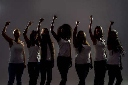 Silhouetted group of diverse women raised their arms, fists while standing over grey background. Diversity, womens rights concept