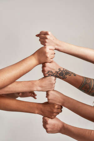 Close up of hands of diverse women putting their fists on top of each other like a team isolated over grey background. Concept of racial unity and relations in society