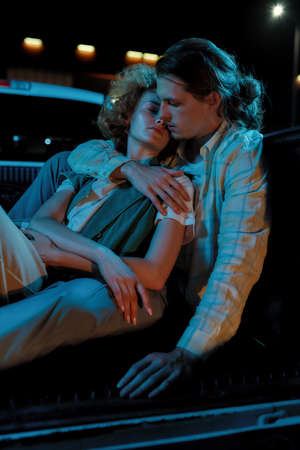A group of two young good-looking white friends of different genders looking at each other while sitting close to each other in an opened car trunk outside on a parking site Foto de archivo