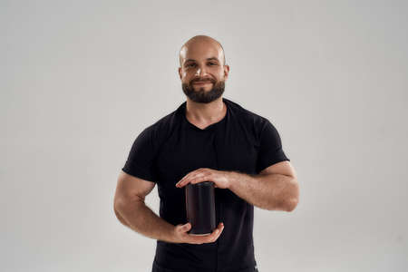 Smiling young muscular caucasian man showing protein bottle