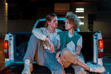 Two young well-dressed white friends of different genders looking at each other while sitting in an opened car trunk outside on a parking site Foto de archivo