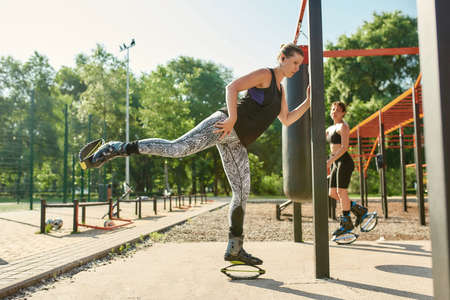 Full length shot of athletic woman in kangoo jumping shoes warming up her body before having workout at street gym yard