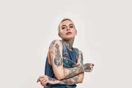 Tattoo and piercing. A white tattooed woman pierced dancing alone wearing a denim overall looking into a camera with her hands crossed on her chest in a motion