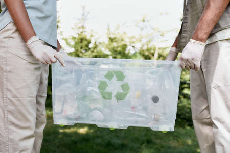 Cropped shot of two volunteers holding recycle bin with plastic waste while standing in the forest or park