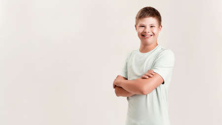 Joyful disabled boy with Down syndrome smiling at camera while posing, standing with arms crossed isolated over white background