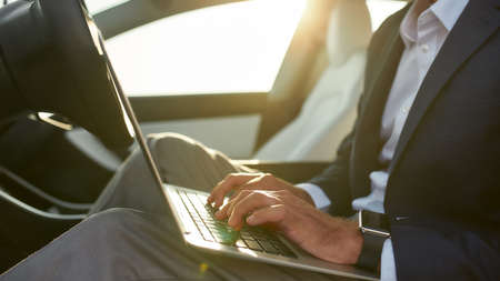 Businessman typing on laptop keyboard in car