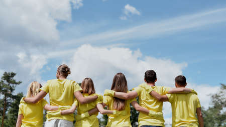 Save the nature. Group of young volunteers wearing uniform and rubber gloves hugging and looking at green forest in front of them, rear view Banque d'images