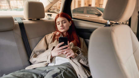 Teenage girl in earphones using her smartphone while sitting on back seat in the car