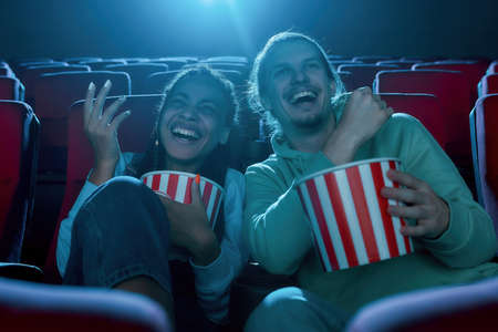 Best friends, young man and woman having fun, sitting at the cinema, watching a movie and eating popcorn