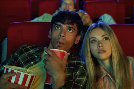 Portrait of young couple, attractive man and woman really interested in watching movie while sitting at the cinema, eating popcorn