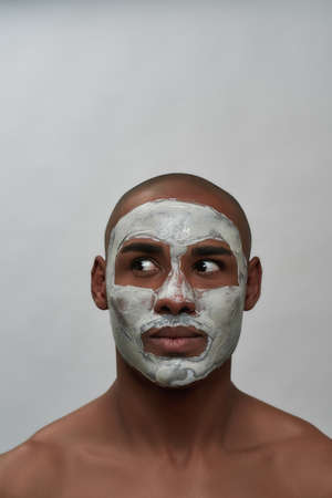 Handsome young african american man looking surprised aside, using facial blackhead removal mask, posing isolated over gray background