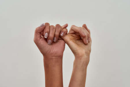 Close up shot of pinky swear. Promise hand gesture isolated over light background