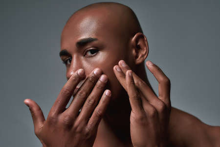 Close up shot of handsome young african american guy squeezing out a pimple on the cheek, posing isolated over grey background
