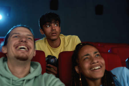 Young guy looking scared, using his video camera while recording a pirated movie at the cinema