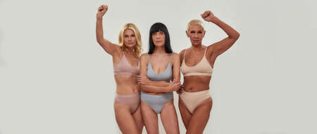 Portrait of three confident mature women in underwear looking at camera while posing together half naked, standing with arms raised isolated over light background