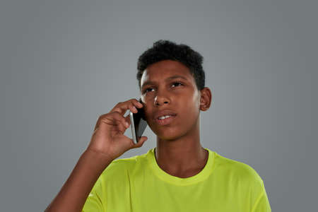 Portrait of a teenage african boy wearing neon t shirt talking by phone while standing against grey background, vertical shot
