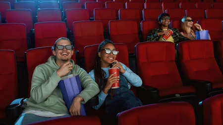 Joyful young couple wearing 3d glasses watching a movie together in cinema auditorium, eating popcorn and drinking soda