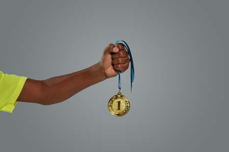 Award of victory. Teenage african boy holding gold medal against grey background
