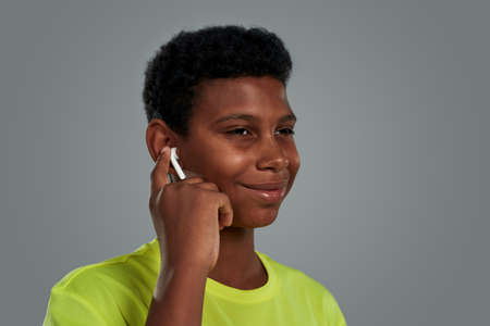 My favourite playlist. Portrait of teenage african boy adjusting wireless earphones and smiling while standing against grey background