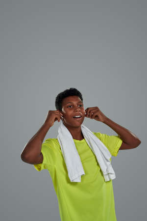 Enjoying music. Teenage sporty african boy wearing wireless earphones with white towel on shoulders posing against grey background