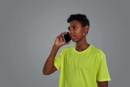Young people and communication concept. Close up shot of a teenage african boy wearing neon t shirt talking by phone while standing against grey background