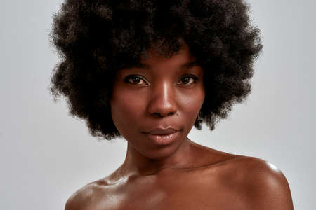 Close up portrait of stunning african american young woman with afro hair and perfect smooth glowing skin looking at camera while posing isolated over gray background