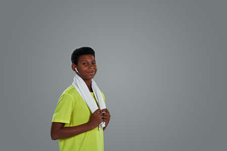 Portrait of a happy teenage sporty african boy in neon shirt with white towel on shoulders wearing wireless earphones looking at camera while posing against grey background