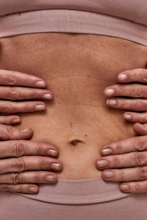 Four hands wrapped around a person belly