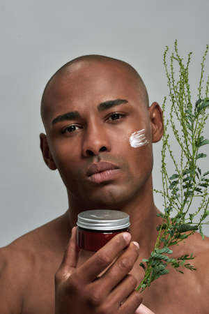 Face of a person holding a facial cream and branch