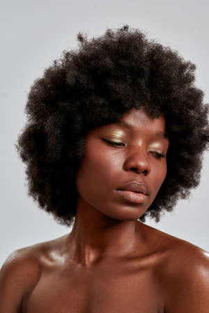 Close up portrait of adorable african american young woman with afro hair and perfect smooth glowing skin looking down, posing isolated over gray background