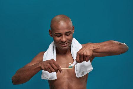 Careful multiethnic male putting toothpaste on a brush 免版税图像