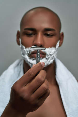 Handsome young african american man with shaving foam applied on his face holding steel razor, posing isolated over gray background 免版税图像