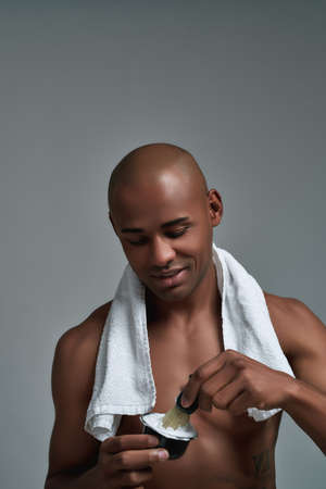 Shirtless cheerful young african american man smiling, using brush while making shaving foam, posing with towel around his neck isolated over gray background
