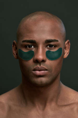 Serious man with dark green under eye patches